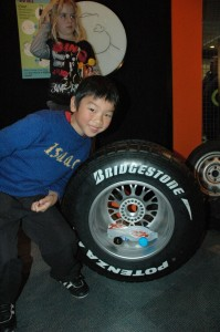 Isaac sizing up his race car's tyres with the F1 Bridgestone one. © Te Papa, 2009.