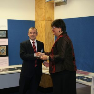 Brian Roche, NZ Post's Chief Executive, hands the Taupo Invert stamp to Te Papa's Acting Chief Executive and Kaihautū, Michelle Hippolite.  Photo reproduced courtesy of NZ Post Group.