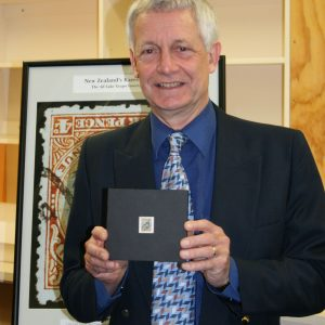 Dr Patrick Brownsey, Te Papa's stamp curator, holding the Taupo Invert.  Image reproduced courtesy of NZ Post Group.