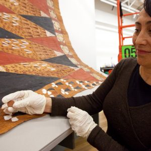 Conservator Rangi Warnes shows one of the powerful magnets used to hold the tapa in place.