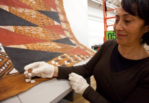 Conservator Rangi Te Kanawa shows one of the magnets used to hold the tapa in place.