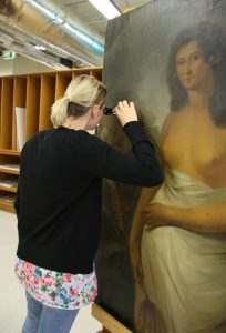 Katherine examining the painting with a hand-held microscope