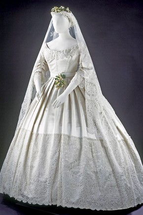 Wedding dress, England, 1865. Silk-satin dress trimmed with Honiton appliqué lace, machine-net and bobbin lace. Worn at the wedding of Eliza Penelope Clay and Joseph Bright, St James's Church, Piccadilly, London, 16 February 1865. Museum no. T.43-1947