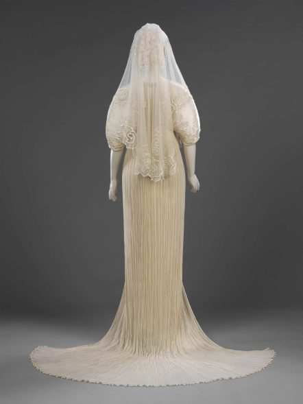 Pleated silk wedding dress and coat, net veil decorated with silicone rubber, by Ian and Marcel, London, 1989. Bequeathed by Ian and Marcel. ©Victoria and Albert Museum / V&A Images