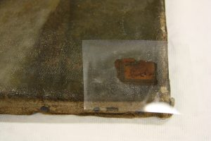 During the removal process. This image shows the paper label coated with a layer of methyl cellulose.  The Mylar on top ensures the methyl cellulose does not 'dry-up'.  Photograph taken by Melanie Carlisle, 2011. © Te Papa