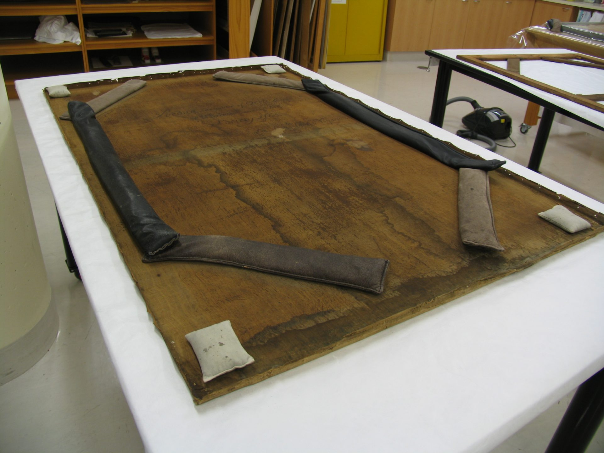 The canvas face down on the table with the stretcher removed (which can be seen on another table in the top right). The leather weights hold the canvas in position while it is loose. Photograph taken by Melanie Carlisle, 2011. © Te Papa.