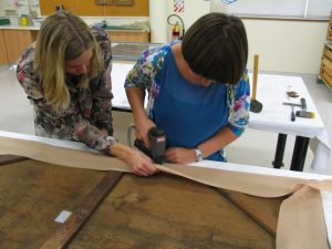 Katherine and I restretching the canvas and attaching the strip lining canvas at the back with staples. Photograph taken by Drew Ward, 2011. © Te Papa.
