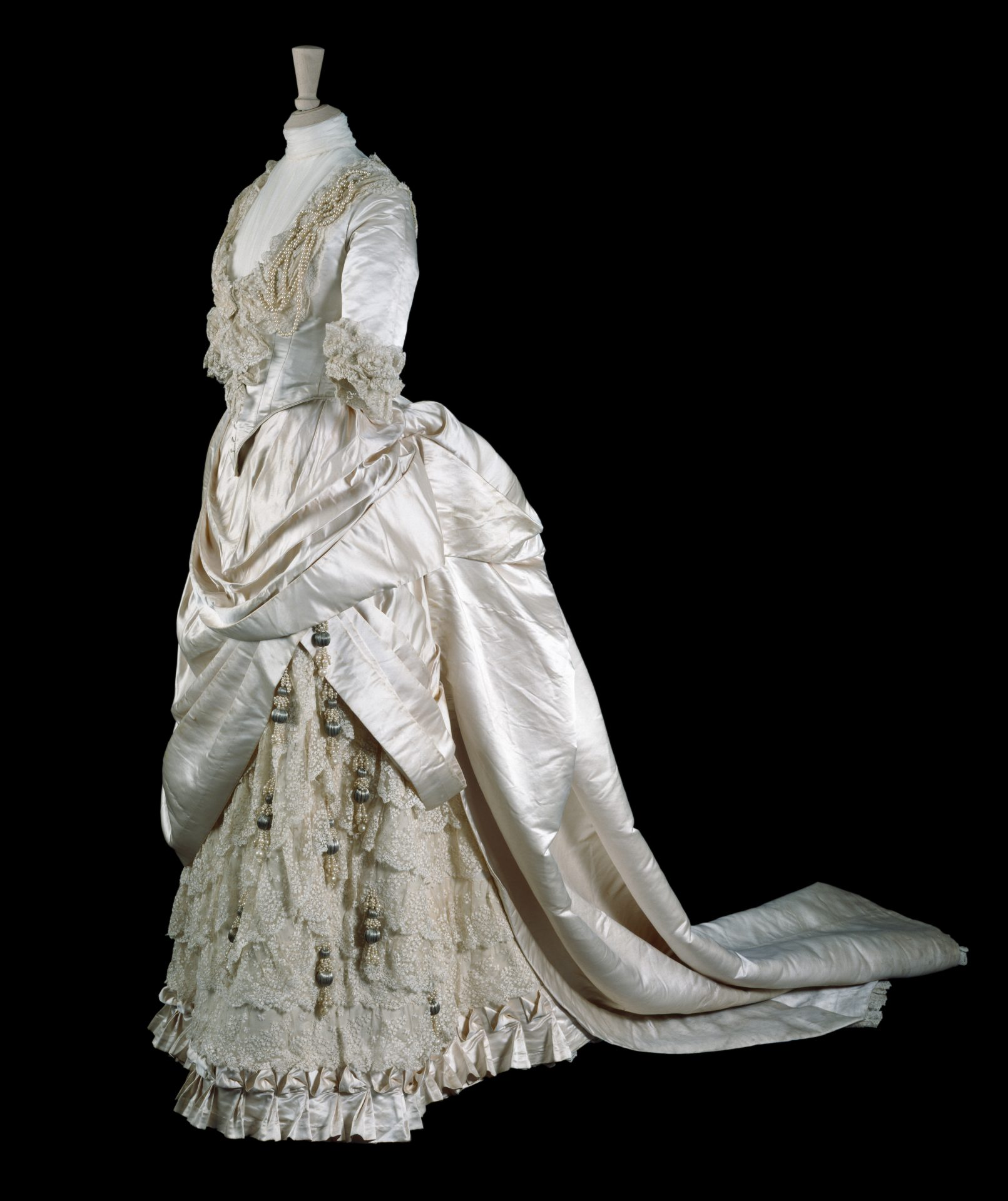 Wedding dress made by Gladman & Womack, London, 1885. Cream silk satin trimmed with embroidered net and pearl beads. Worn by May Primrose to marry Major Herbert Littledale on 10 June 1885 in Cheltenham. Given by the Hon.S.F. Tyser