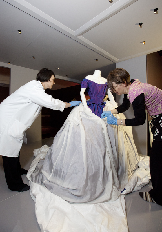 Rachael Collinge from Te Papa and Sarah Scott from the V&A remove the protective covering to reveal the splendour of Dita von Teese's Vivienne Westwood gown. Photo: Kate Whitley, Te Papa.