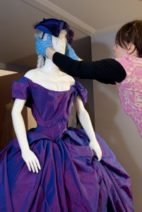Sarah adds a final touch to Dita von Teese's outfit - a jaunty tricorne hat by Stephen Jones. Photo: Kate Whitley, Te Papa.