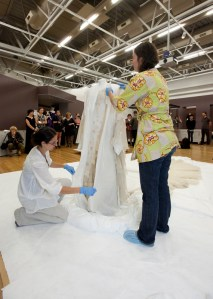 Keira Miller and Anne Peranteau remove the mannequin's protective coverings. Photo: Kate Whitley, Te Papa