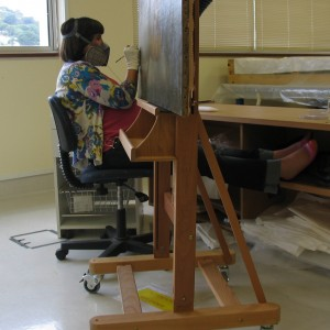 Retouching along the bottom edge of the painting (with my feet up!).  Photograph taken by Matthew O'Reilly, © Te Papa.