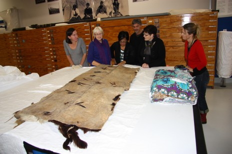Te Papa staff look at the huru kurī, cloak stitched from whole dog skins, on loan from Puke Ariki. Photograph by Moana Parata, copyright Te Papa.