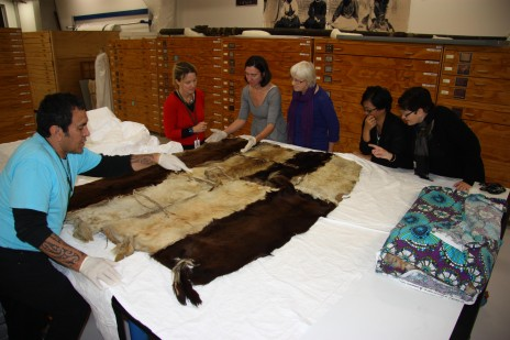 Te Papa staff look at the huru kurī cloak in Te Whare Pora, the collection store. Photograph by Moana Parata, copyright Te Papa.