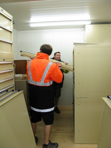 Steve McStay and Paul Simpson sliding an empty plan drawer into the unit.