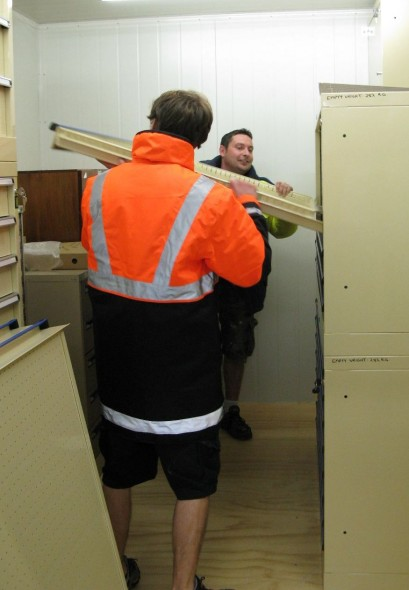 Steve McStay and Paul Simpson sliding an empty drawer into the plan chest unit.
