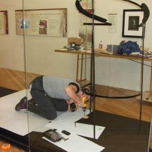 Sam Wallis preparing the case and complex mount for the huru kuri, dog skin pelt cloak, on loan from Puke Ariki, photograph by Pamela Lovis, copyright Te Papa 2012.
