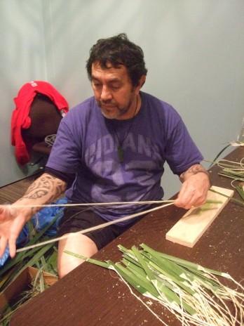 Mark Sykes preparing the muka. Photograph by Matariki Williams. Te Papa.
