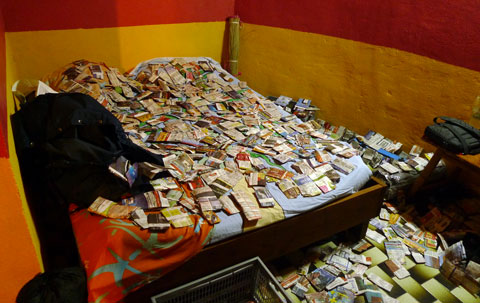 All available space in our lodgings was often given over to drying specimens. Louis's bed is somewhere under these paper packets.  Photo Leon Perrie. © Te Papa.