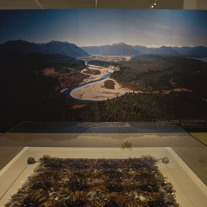 The cloak on display adjacent to a Brian Brake image of Taramakau River. The photograph emphasises the colours of Papatūānuku (the earth mother) complimenting the design and colors of the feathers on the cloak. Image courtesy of National Museum of China.