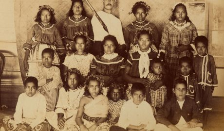 A group of Tokelau children and a white man stare at the camera with blank expressions