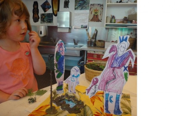 April age 4. Working on her diorama using cardboard hand drawn figures, mirror 'pool', fabric, plastic trees.Photographer: Tai Tamariki, © Tai Tamariki