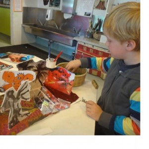 Max, age 4.Creating his diorama with a mirror 'river', magazine cut outs, fabric, and hand drawn 'God of Death'.Photographer: Tai Tamariki, © Tai Tamariki