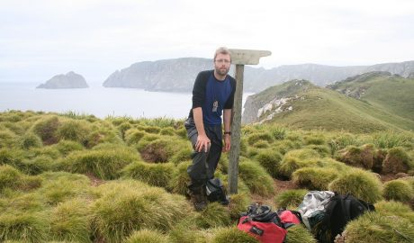 Antony Kusabs, Collection Manaqger at the South Promontory sign post with Alert Stack and South-west promontory in background. Snares Islands, North East Isalnd. Image: Jean-Claude Stahl, Te Papa.