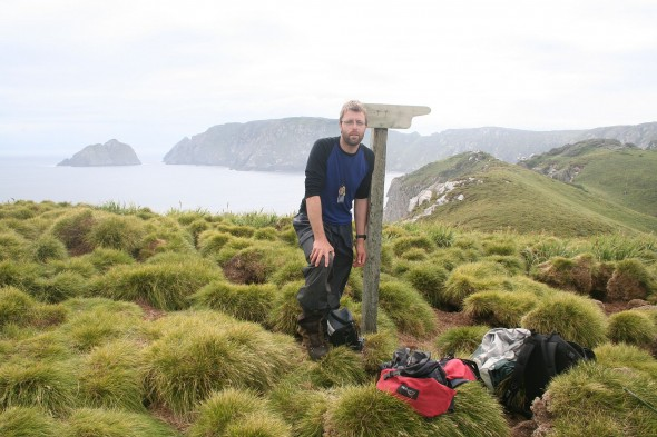 Te Papa Collection Manager, Antony Kusabs at the South Promontory sign post with Alert Stack and South-west promontory in background. Snares Islands, North East Island. Image: Jean-Claude Stahl, Te Papa.