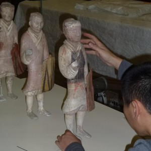 Installing a pottery soldier. Photographer: Justine Olsen © Te Papa