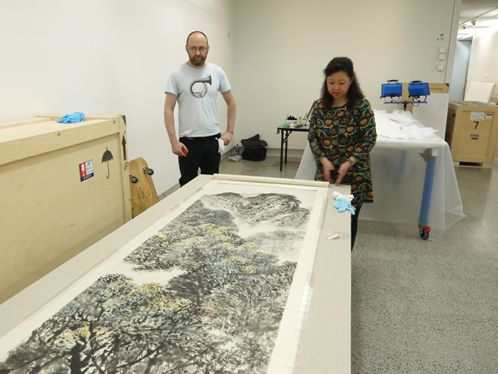 James Kirk, framer, and Ms. Zhang Yulan installing one of Shi Lu's large scroll paintings.