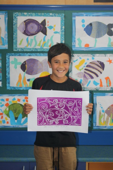 Ian Levi Ware proudly shows his awesome linocut print. Photographed by Makaira Waugh © Te Papa