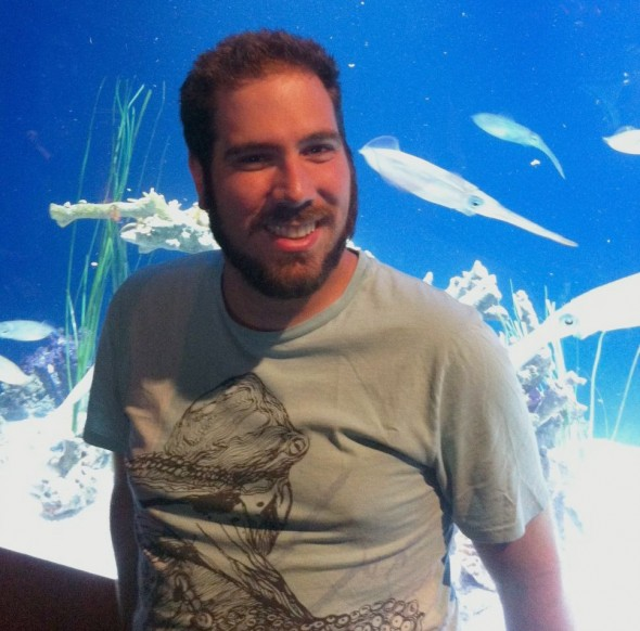 Aaron visiting the Monterey Bay Aquarium in California. The squid in the tank behind him are big-fin reef squid. And that is an octopus on his t-shirt. As Aaron explains '…my passion for cephalopods is prominent in my attire as well as my household belongings.'  © Aaron Boyd Evans