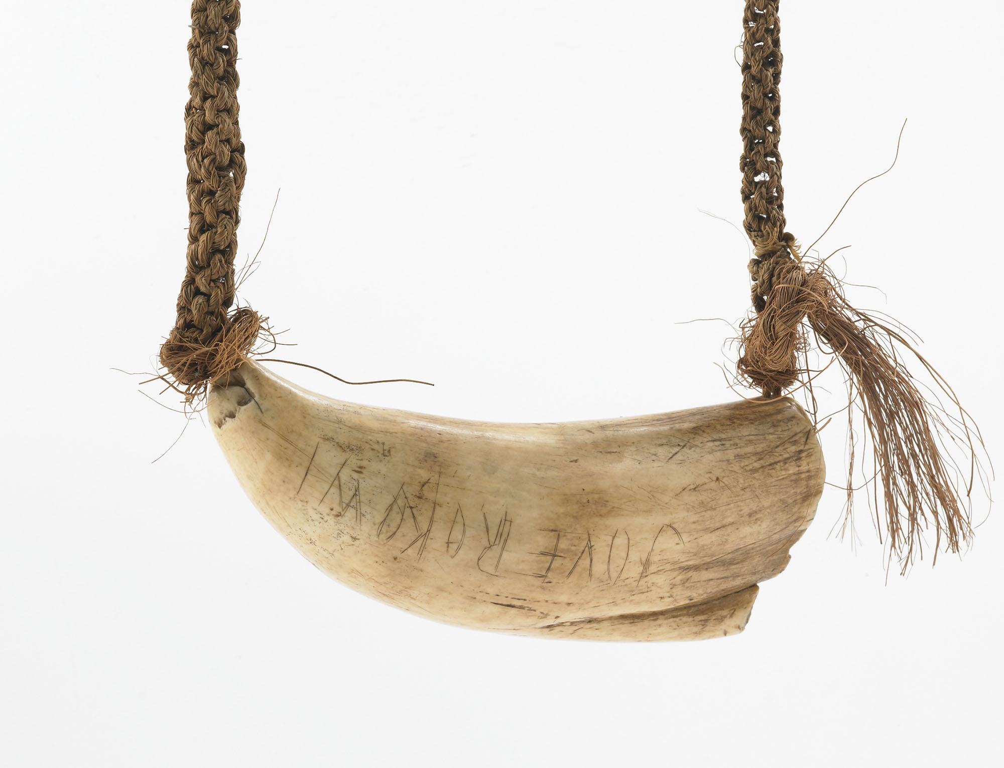 "Whale's tooth attached to a braided necklace. On the tooth is scratched ""JOVE ROKOWI"""