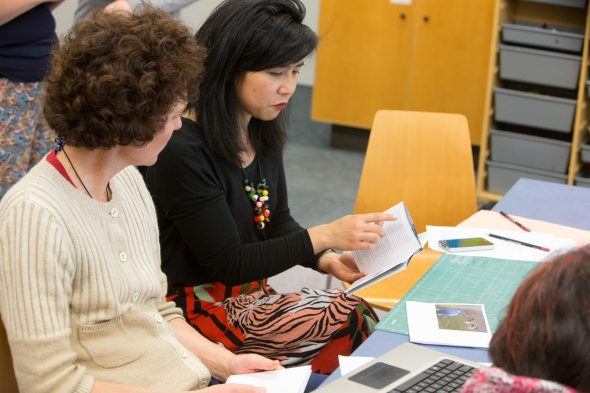 Zine-making expert Kerry-Ann Lee (right) discusses the layouts and formats of a folded zine with Susan Waugh, writer of the 'Travels with Besty' zine. Photo Norm Heke, Copyright Te Papa