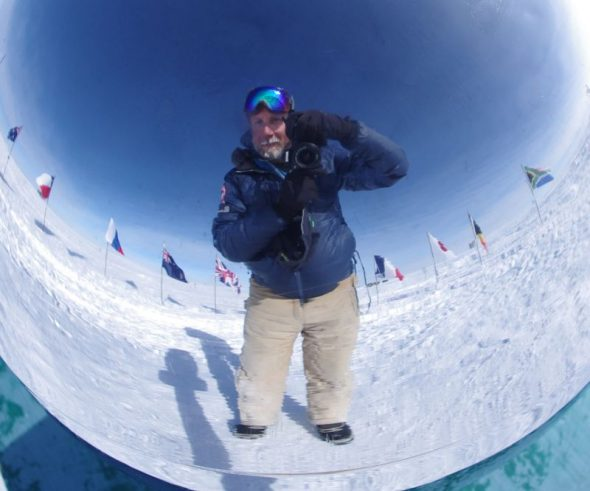 The author reflected in the ceremonial South Pole marker. The marker is partially surrounded by the flags of the 12 original signatory nations to the Antarctic Treaty. The New Zealand flag is to my left. Image: Colin Miskelly