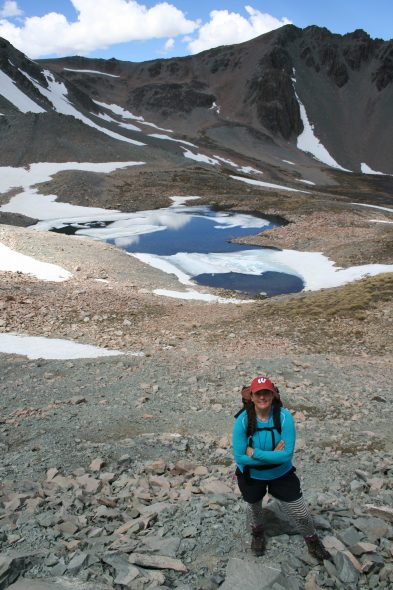 Perks of the job: Here I am by a partially-frozen tarn near Mt Potts. A beautiful site, but not a lot of plants growing up here. Photo by Ant Kusabs © Te Papa.