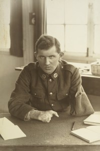 Untitled [portrait of a WWI soldier (Allan McMillan) with an amputated arm sitting at a desk at Oatlands Park, Surrey, England], 1918, England, maker unknown. Te Papa (O.031468)
