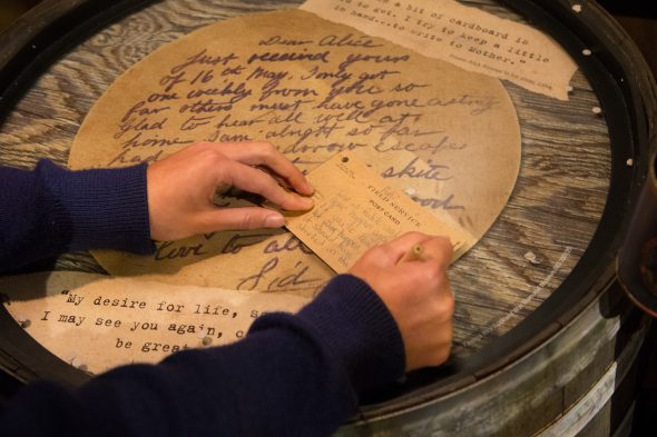 A young visitor tries her hand at writing a message home from Gallipoli. Photo by Norm Heke, Te Papa