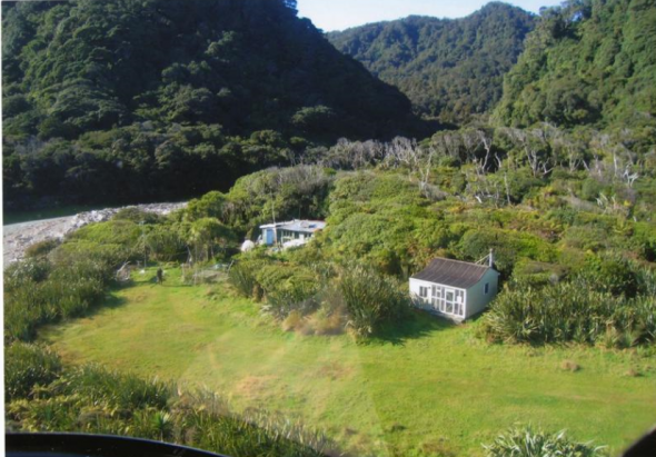 •An aerial view of the 'settlement' at Gorge River mouth, with Robert Long & Catherine Stewart's house on the left, and the Department of Conservation hut on the right. Image: Robert Long