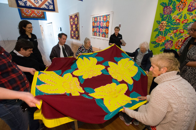 Tour participants sitting around large tivaevae quilt, feeling stiches and shapes.