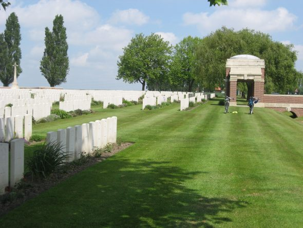 K.L. Adam's headstone under the shade of a tree, New Irish Farm Cemetery, Ieper, West-Vlaanderen, Belgium photo taken by Sue and Colin Brown