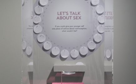 Display case with one contraceptive pill stating 'the pill that changed the world' against a backdrop of visitors' comments 'Let's talk about sex'