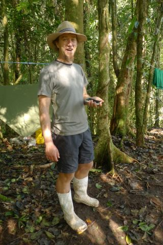 Gumboots were de rigueur for several of the international participants. Here, Sydney Botanic Garden's Matt Renner models Honiara's finest, choppered in midway through the expedition. Rain and grey skies meant tramping boots festered. Matt was also a patron of Honiara's milliners. Photo Leon Perrie. (c) Te Papa.