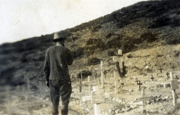 A soldier stands by a cemetery at Anzac cove before departing. The large cross at the right has five names on it. Photograph by Norman Henry Prior. Wairarapa Archives (11-72/4-2-19.digital)