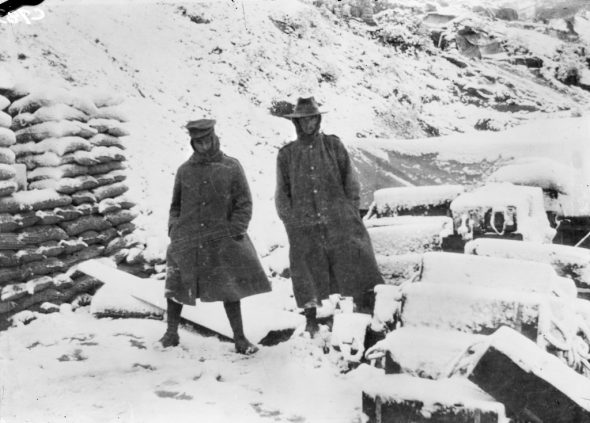 Rugged up in warm greatcoats, two unidentified Australian soldiers stand in the snow outsidea dugout on Gallipoli, circa November 1915. Photographer unknown. Australian War Memorial (C00783)