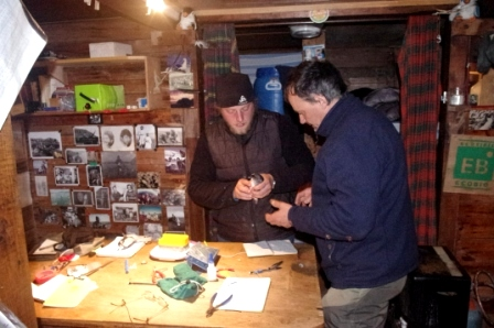 Aymeric Fromant and Charly Bost preparing to attach a GPS tag to a common diving petrel, inside the hut on Ile Mayes. Image by Colin Miskelly, copyright IPEV/Te Papa