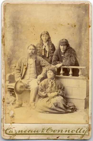 Standing at rear: Hāna Cootes, Hera Cootes. Seated front: Hemi Tiapo Cootes, unidentified woman. Cabinet card portrait of the Cootes family of Porirua and Otaki, taken 1883-1885 by Cazneau & Connolly of Lambton Quay, Wellington