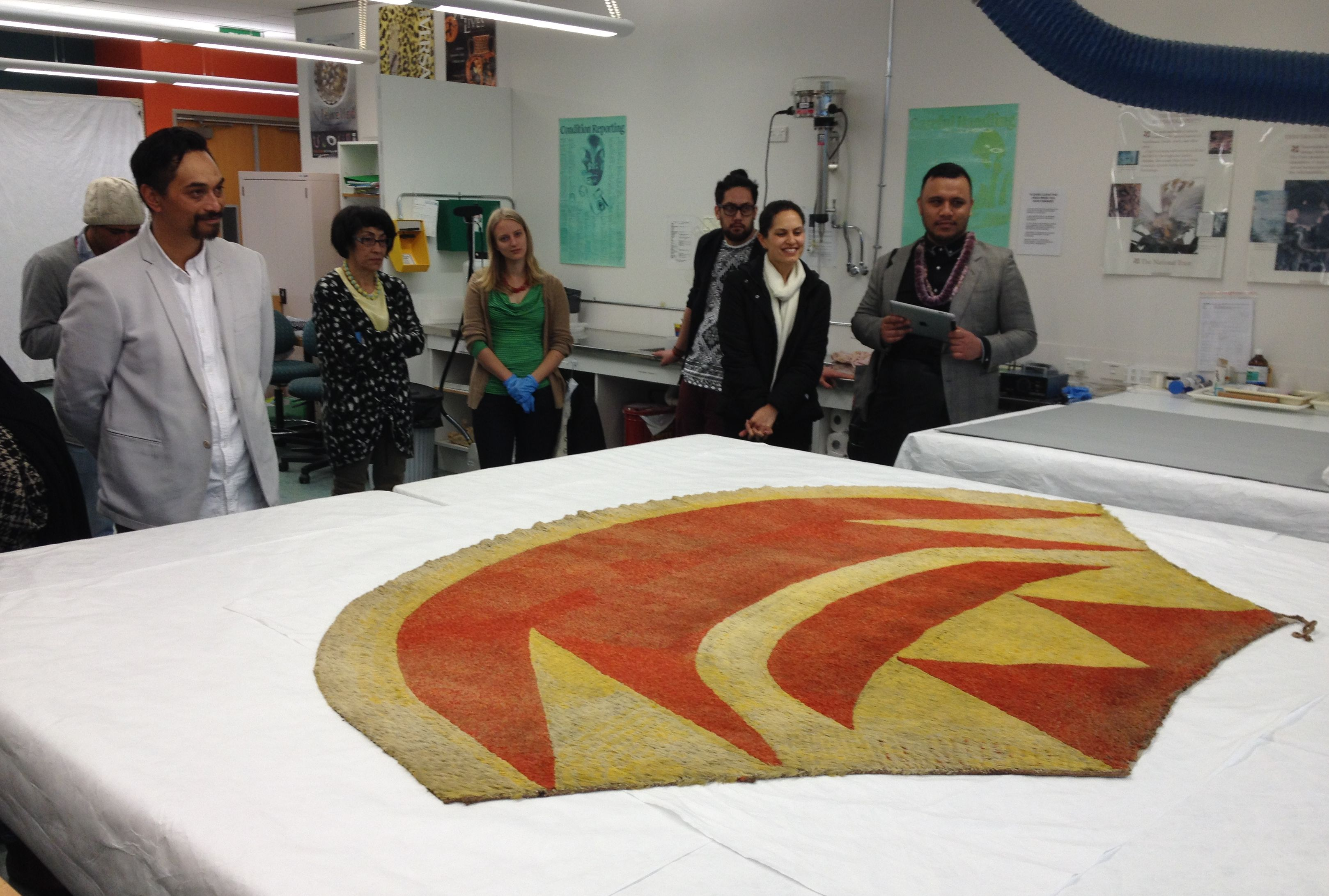 Group of people look at the cloak lying on a table