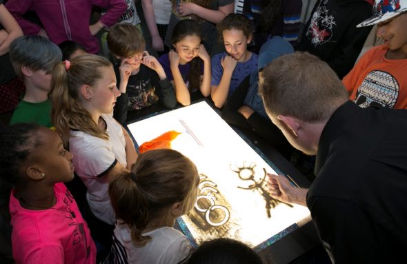 A Te Papa educator demonstrates positive and negative space. Photograph by Norm Heke. Te Papa